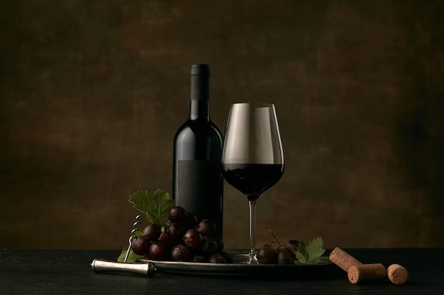 Front view of tasty fruit plate of grapes with the wine bottle, cheese, fruits and glass on dark  background