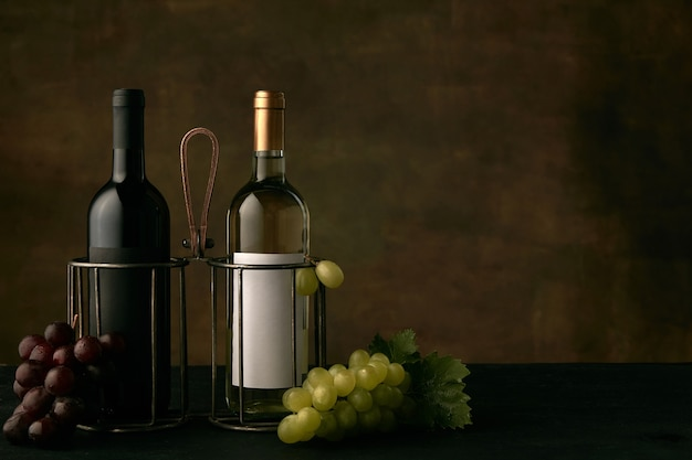 Front view of tasty fruit plate of grapes with the wine bottles on dark studio background, copy space to insert your text or image. gourmet food and drink.
