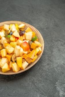 La gustosa insalata di frutta vista frontale è composta da frutta fresca sul tavolo grigio frutta molti freschi