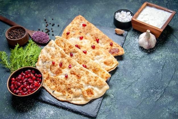 어두운 표면에 고기와 석류가 있는 맛있는 구타브 핫케이크 전면 보기