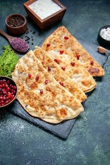 어두운 표면에 고기와 석류가 있는 맛있는 구타브 얇은 핫케이크 전면 보기