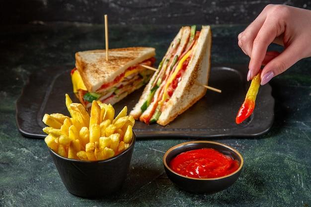 フライドポテトが女性の暗い表面に食べられる正面図のおいしいハムサンドイッチ