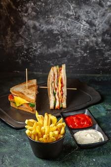 Вкусные бутерброды с ветчиной и картофелем фри, вид спереди, едят на темной поверхности