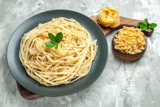 Vista frontale gustosa pasta italiana su cibo di pasta di foto di pasto di colore chiaro