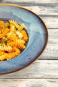 Vista frontale gustosa pasta italiana insolita pasta a spirale cotta su scrivania in legno grigio cucina pasto cena piatto di pasta