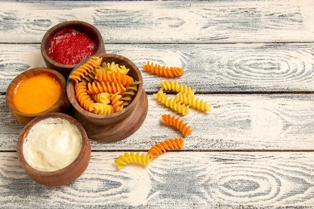 Vista frontale gustosa pasta italiana insolita pasta a spirale cotta sulla scrivania in legno grigio che cucina pasto piatto di pasta cena