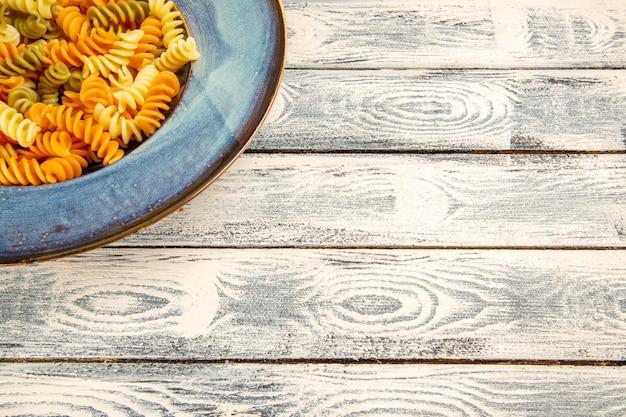 Вид спереди вкусная итальянская паста, необычная приготовленная спиральная паста на сером деревянном столе, приготовление обеда из теста, блюдо из макарон