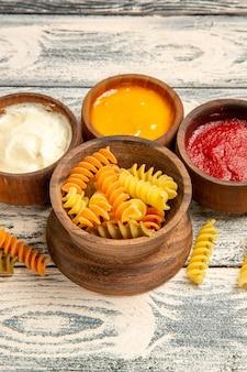 正面から見たおいしいイタリアン パスタ珍しい調理されたスパイラル パスタ グレーの木の机の料理の食事パスタ皿ディナー