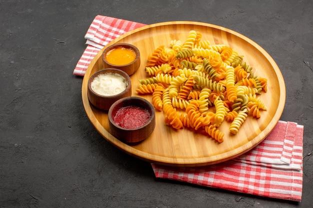 正面から見たおいしいイタリアン パスタ、暗いスペースに調味料を使った珍しい調理済みスパイラル パスタ