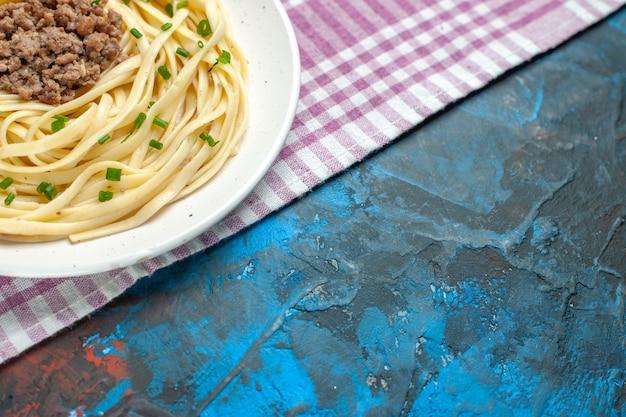 青い皿の肉生地の色の食べ物にひき肉を入れた正面のおいしいイタリアン パスタ