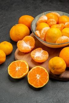 Vista frontale gustosi mandarini succosi all'interno del piatto sullo sfondo grigio agrumi esotici foto a colori arancia acida