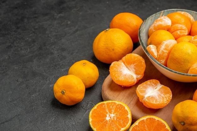 Вид спереди вкусные сочные мандарины внутри тарелки на сером фоне экзотические цитрусовые цвет фото кислый апельсин