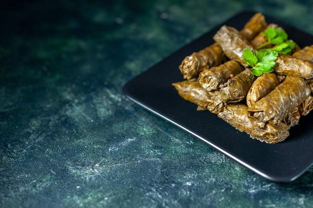 Vista frontale gustoso dolma foglia su sfondo scuro calorie olio cena cibo pasto insalata piatto di carne