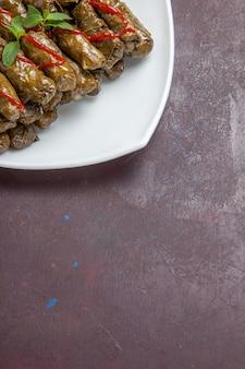 Вид спереди вкусное блюдо из мясного фарша из листьев долмы внутри тарелки на темном столе, мясное блюдо, обед из листьев