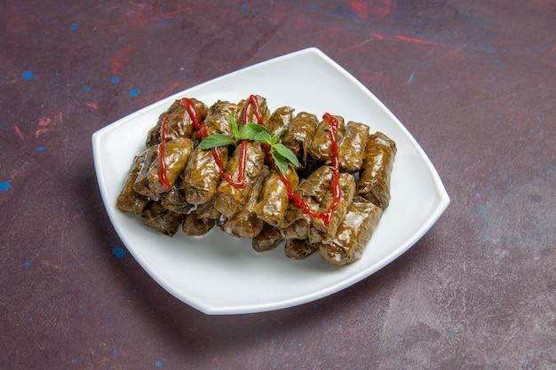 Вид спереди вкусное блюдо из фарша из листовой долмы внутри тарелки на темном пространстве