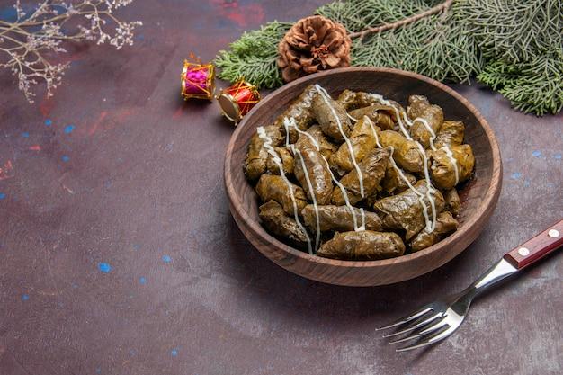 어두운 공간에 갈색 접시 안에 전면보기 맛있는 잎 돌마 고기 요리
