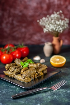 Front view tasty leaf dolma with red tomatoes on dark background calorie oil dinner food salad dish meat restaurant meal