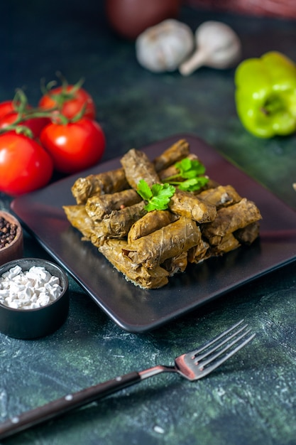 Front view tasty leaf dolma with tomatoes on dark floor calorie oil dinner food salad dish meat restaurant meal