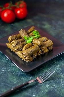 전면보기 어두운 배경에 토마토와 맛있는 잎 돌마 칼로리 오일 저녁 식사 음식 식사 샐러드 요리 고기 레스토랑