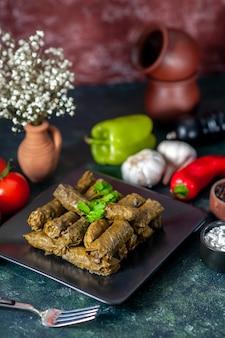 Вид спереди вкусной листовой долмы с помидорами на темном фоне калорийность масла ужин еда салат мясо ресторан еда