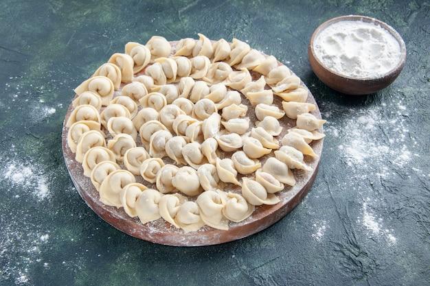 Vista frontale gustosi gnocchi con farina su superficie scura
