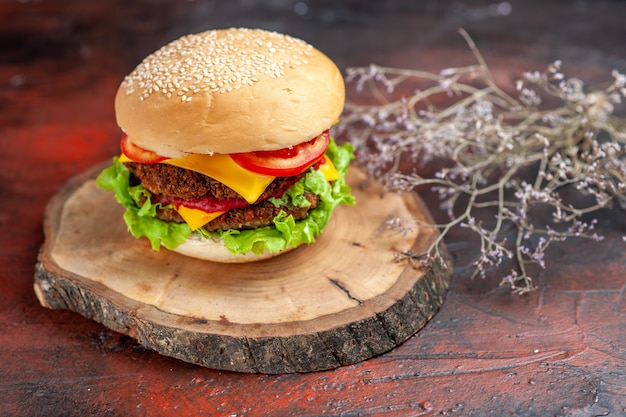 暗い背景にチーズとサラダを添えた正面図のおいしいミートバーガー
