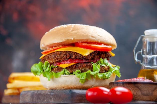 Vista frontale gustoso hamburger di carne con patatine fritte su sfondo scuro