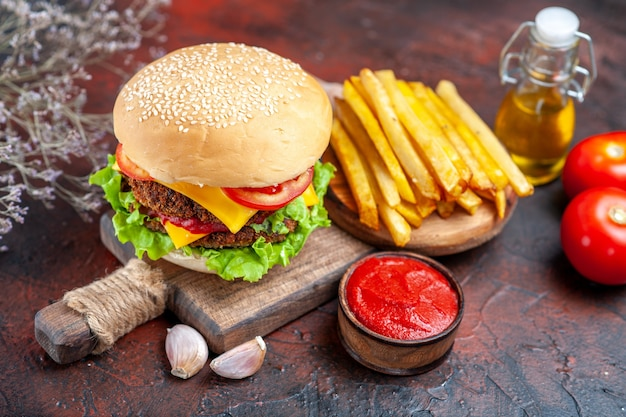 Vista frontale gustoso hamburger di carne con patatine fritte sul panino panino scuro scrivania fast-food