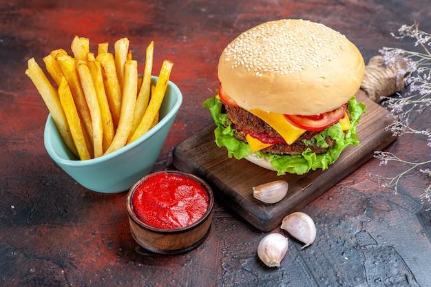 Vista frontale gustoso hamburger di carne con patatine fritte sul pavimento scuro