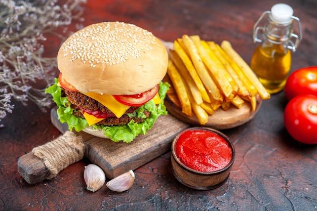 Вид спереди вкусный мясной гамбургер с картофелем фри на темной столовой булочке сэндвич фаст-фуд