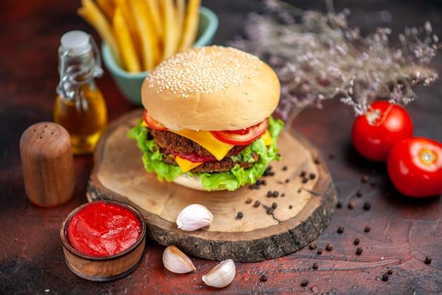 Вид спереди вкусный мясной бургер с картофелем фри на темном столе
