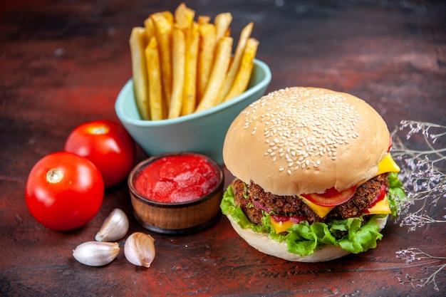 Вид спереди вкусный мясной бургер с картофелем фри на темном фоне