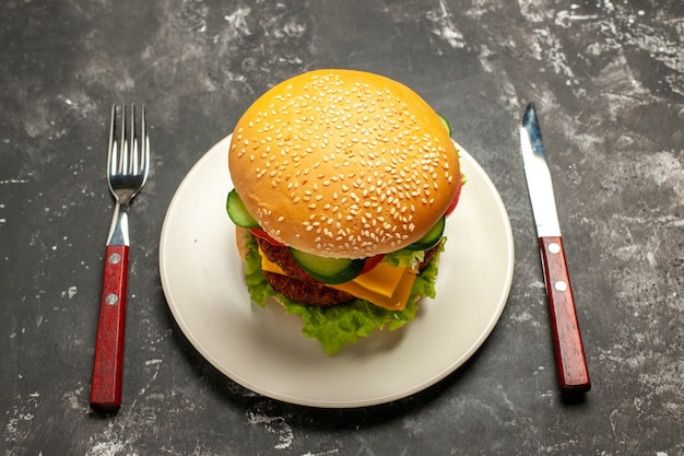 Front view tasty meat burger with vegetables on dark surface bun sandwich fast-food