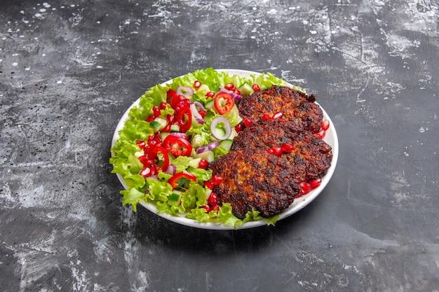 新鮮なサラダと正面のおいしい肉カツレツ