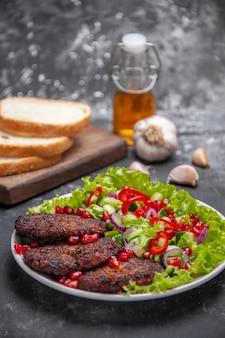 Vista frontale gustose cotolette di carne con insalata e pane