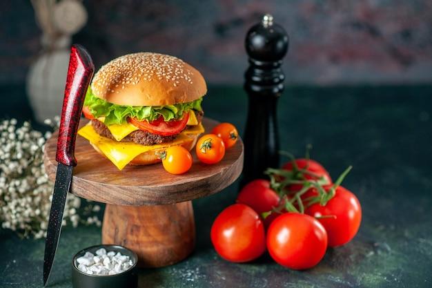 Вид спереди вкусный мясной гамбургер с ножом, помидорами и перцовым шейкером на темном фоне