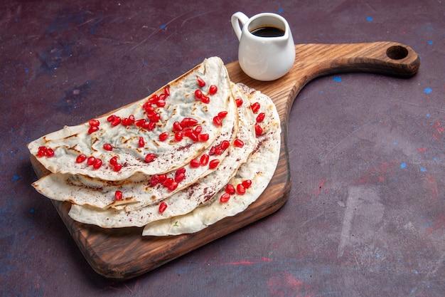 Pitas qutabs di carne gustosa vista frontale con melograni rossi freschi su pita di pasta di carne superficie viola scuro