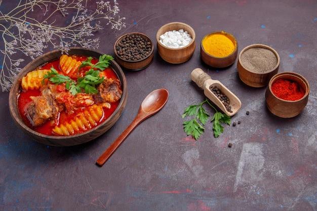 暗い表面の料理のスープ食品ディナーソースにさまざまな調味料を加えた正面図のおいしいミートソース