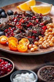 Вид спереди вкусные кусочки мяса жареная еда с фруктами внутри тарелки на темном фоне