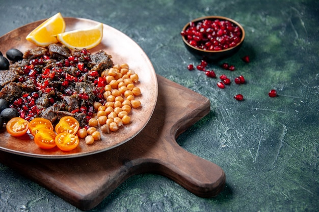 Вид спереди вкусные кусочки мяса, жареная еда с фруктами внутри тарелки на темно-синем фоне