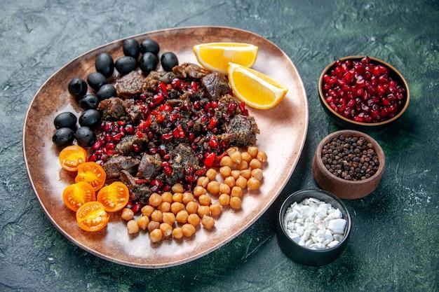 진한 파란색 배경에 접시 안에 콩 포도와 레몬 조각으로 튀긴 전면보기 맛있는 고기 조각