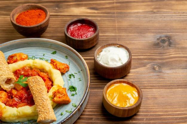 茶色の机の皿にマッシュ ポテトと調味料を入れたおいしい肉のスライスの正面図肉料理ポテト パン料理