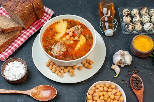 正面図おいしい肉スープは、暗いテーブルの上にジャガイモの肉と豆で構成されています