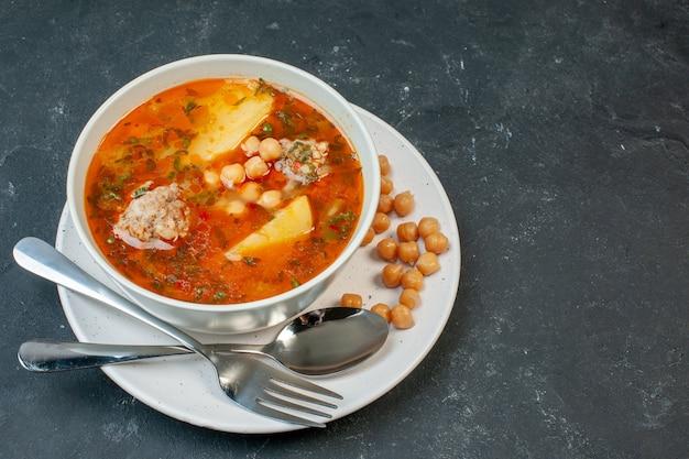 暗いテーブルの上に豆の緑とジャガイモを添えた正面図のおいしい肉スープ