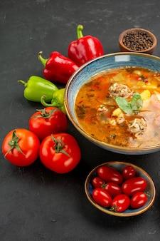 暗い背景に新鮮な野菜を使ったおいしい肉のスープを正面から見る