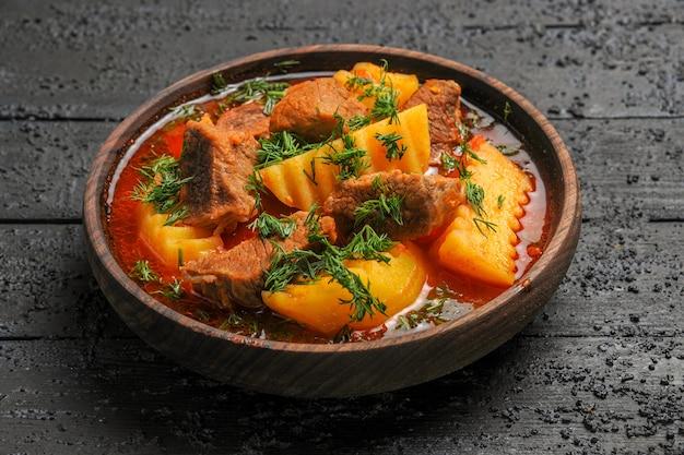 Вкусный мясной суп с картофелем и зеленью на темном столе, соус для мясного блюда, вид спереди