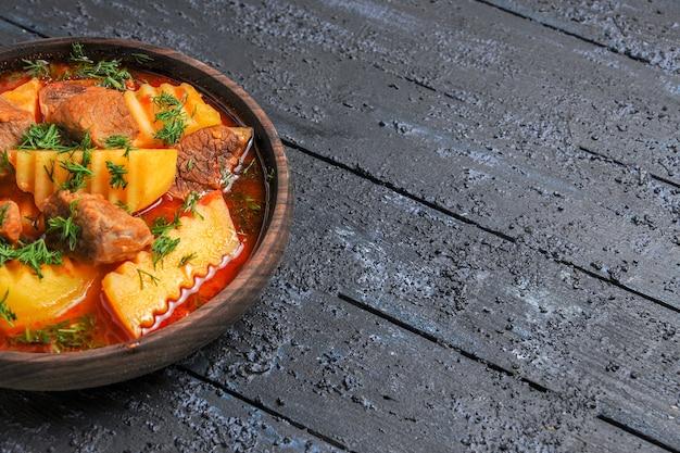 Вид спереди вкусный мясной суп с картофелем и зеленью на темном столе с мясным соусом