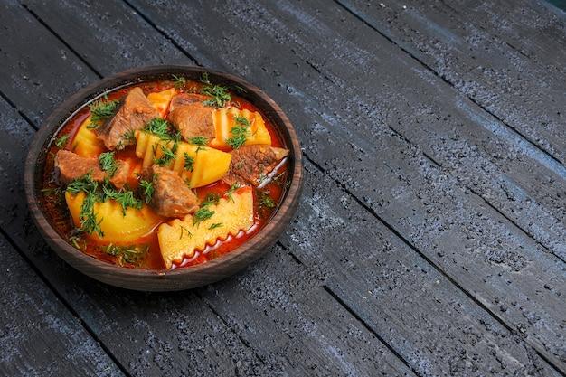 Vista frontale gustosa zuppa di carne con patate e verdure sul pasto di salsa di piatto di carne piano scuro