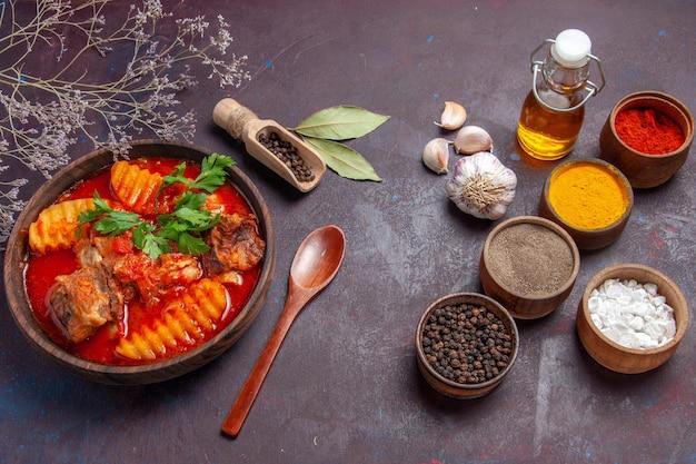 Vista frontale gustosa zuppa di carne con condimenti su salsa di cena di cibo zuppa di superficie scura