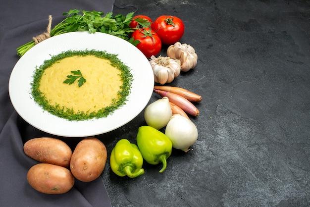 Вид спереди вкусное пюре с зеленью и свежими овощами на темном пространстве